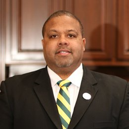 man with short hair wearing suit and green and gold tie