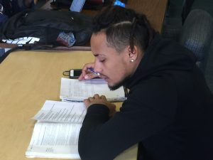 male student taking notes sitting at a table
