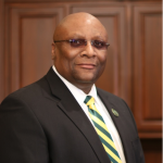 man with glasses wearing a suit with green and gold tie