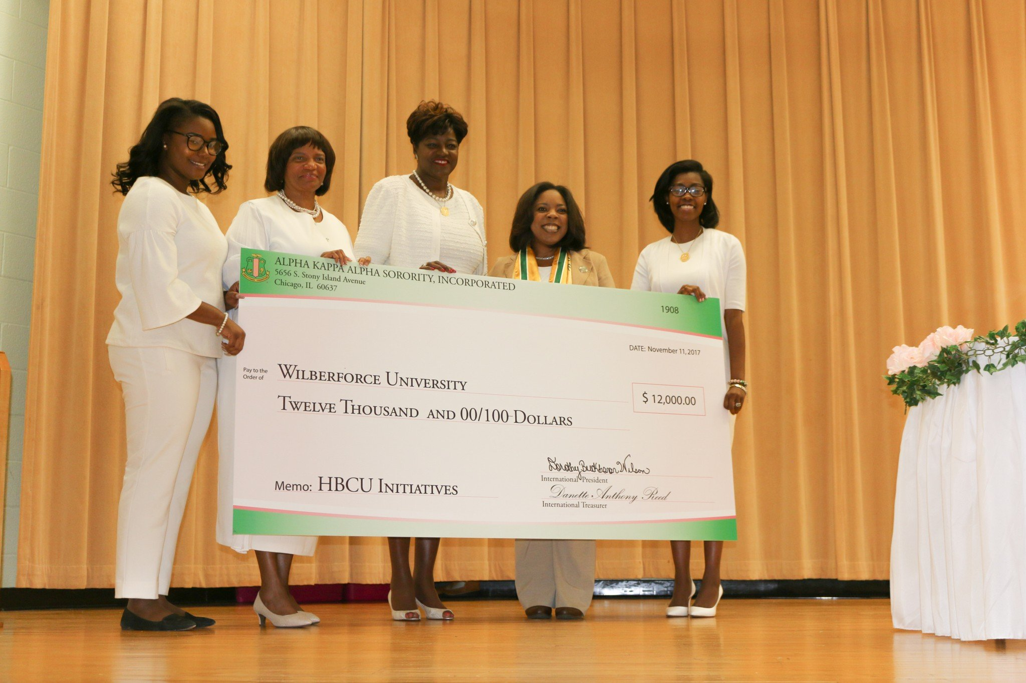 Women on stage hold large check