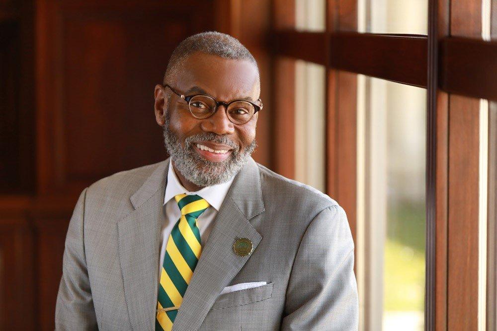 president of university wearing glasses and green and gold tie smiling